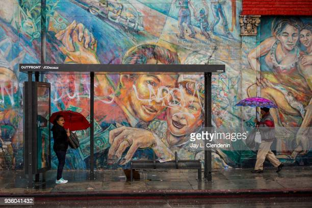 With a classic Boyle Heights neighborhood mural along Soto Street as a backdrop Angelenos deal with a lingering rain storm over Los Angeles CA March...