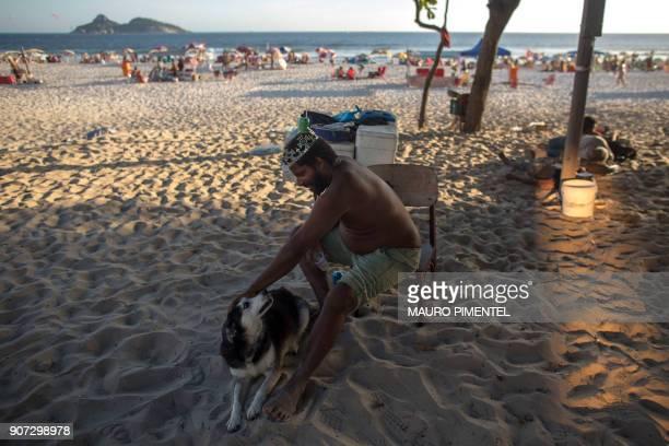 With a crown on his head Marcio Mizael Matolias plays with his dog called Humana at Barra da Tijuca beach in Rio de Janeiro Brazil on January 18 2018...