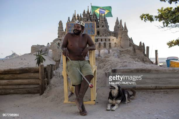 With a crown on his head Marcio Mizael Matolias sits next to his dog called Humana on a throne in front of his sand castle despite the 40degree heat...