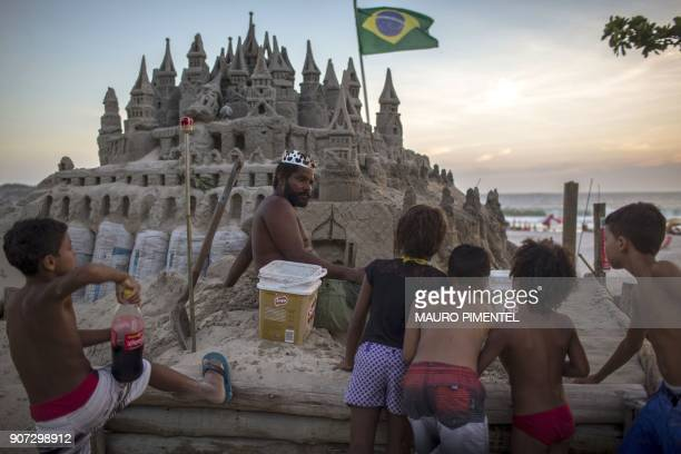 With a crown on his head Marcio Mizael Matolias speaks with children who are interested in his sand castle at Barra da Tijuca beach in Rio de Janeiro...