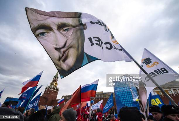 With a flag depicting President Vladimir Putin proKremlin activists rally at the Red Square in Moscow on March 18 to celebrate the incorporation of...