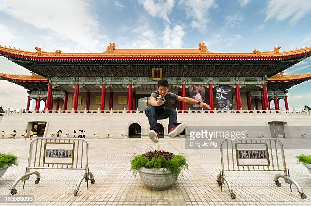 With a GoPro camera in hand, a tourist from Singapore strikes a pose in front of Taiwan's premier performing arts venue, 2012