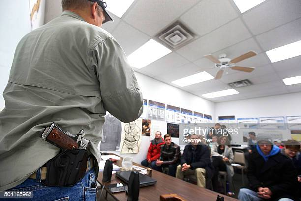 With a gun on his hip gun instructor Mike Stilwell demonstrates an semi automatic hand gun as as he teaches a packed class to obtain the Utah...