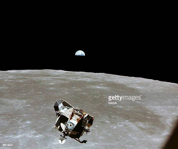 With a halfEarth in the background the Lunar Module ascent stage with Moonwalking Astronauts Neil Armstrong and Edwin Aldrin Jr approaches for a...