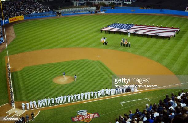 With a large American flag adorning centerfield the players line up along the Yankee Stadium first base line in a pregame ceremony honoring the...
