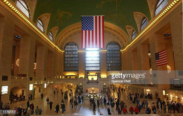With a large American flag hanging from the ceiling, people walk through Grand Central Terminal October 9, 2001 in New York City. In the wake of the...