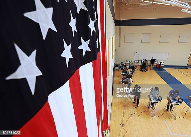 With a large American flag on the wall, people cast their ballot in the presidential election at Freedom Academy elementary school on November 8,...
