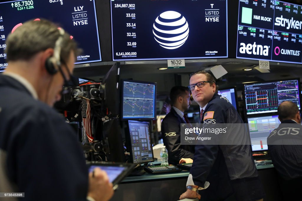With a logo and trading information for AT&T behind them, traders and financial professionals work ahead of the closing bell on the floor of the New York Stock Exchange (NYSE) June 13, 2018 in New York City. Following news today that the Federal Reserve raised interest rates a quarter percentage point, the Dow Jones Industrial Average was down 119 points at the close.