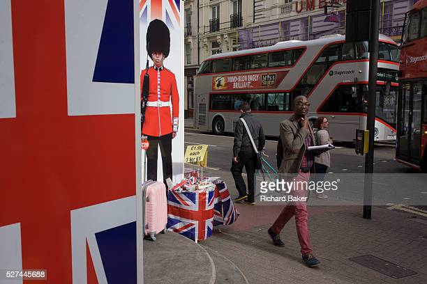 With a London Routemaster bus in the background a successful young black man walks past the image of a Coldstream guardsman and Union Jack flag that...