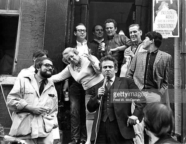With a microphone in his hand American author Norman Mailer makes a face outside the Theatre de Lys on the occasion of the 100th performance of the...