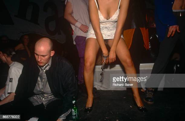 With a pair of handcuffs attached to one wrist an unidentified young woman dances next to a drunk man on 21st June 1997 in London England