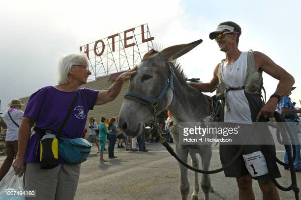 With a pat on the head from a fan Kirt Courkamp of Pine right celebrates winning the 29 mile race with his donkey Mary Margaret middle as the two...