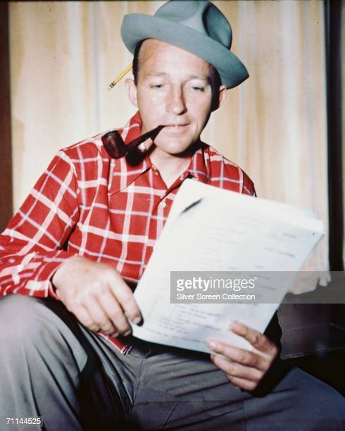 With a pencil tucked into his hat American singer and actor Bing Crosby reads through a script circa 1950