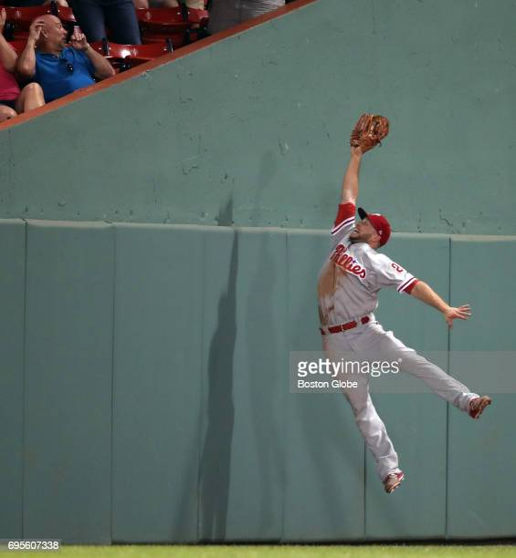 With a potentially game-winning Red Sox run on second base, Phillies left fielder Daniel Nava makes a leaping catch on a fly ball hit by Jackie...