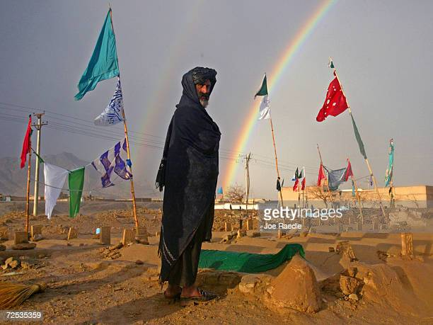 With a rainbow in the background an Afghan man visits graves February 21 2002 at the al Qaeda cemetery in Kandahar Afghanistan More than 80 Arab...