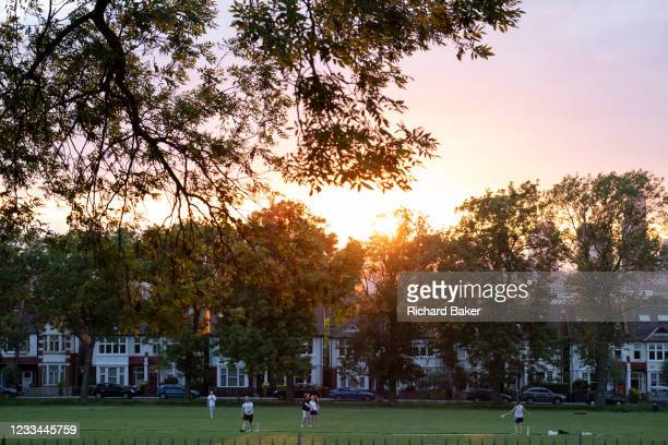With a setting sun sinking below a line of homes and ash trees, a group of friends play a game of informal cricket in Ruskin Park, a public green...
