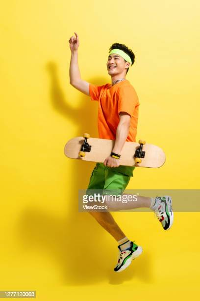 with a skateboard bouncing dynamic young man - ランニングショートパンツ ストックフォトと画像