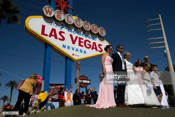 With a small makeshift memorial for Sunday's mass shooting victims below the 'Welcome to Fabulous Las Vegas' sign a wedding party poses for photos by...
