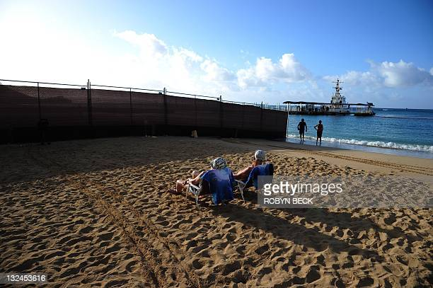 With a US Coast Guard ship docked just offshore a couple sunbathes beside a temporary security barrier on the beach in front of the Hilton Hawaiian...