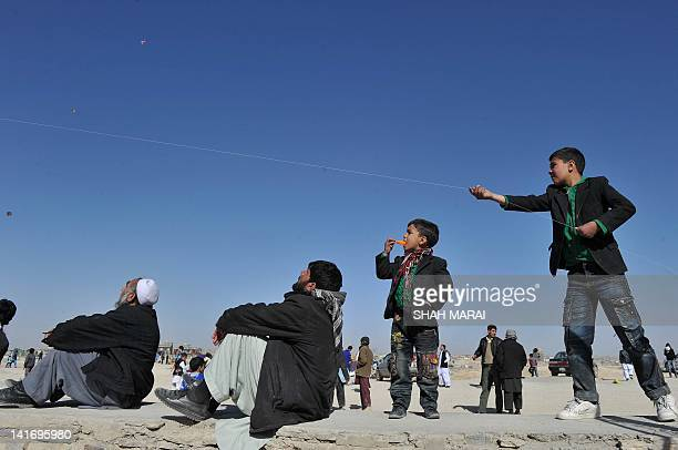 TO GO with AfghanistansocialleisureNewYear by Joris Fioriti In this picture taken on March 21 2012 an Afghan teenager flies his kite as men watch on...