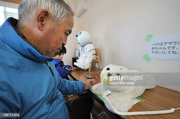 JapandisastertsunamirobotFOCUS by Shingo Ito Hiroshi Onodera displaced by the March 11 tsunami disaster looks at a therapeutic robot baby seal called...