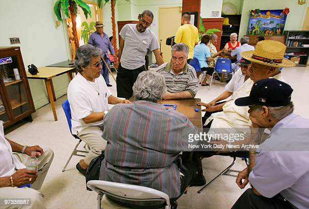 With air conditioners and fans giving them relief from the heat people play dominoes at the Leonard Covello Senior Center on E 109th St in Manhattan...