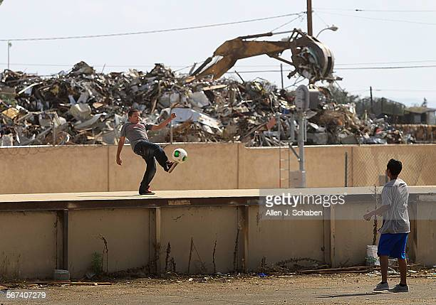 With airplanes taking off overhead heavy machinery piles up a large stack of metal at the Main St Recycling Yard while Abraham Solis left and Kenneth...