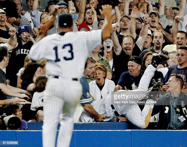 With Alex Rodriguez backing him up, Derek Jeter dives into Stadium stands to make run-saving catch by Boston's Trot Nixon in 12th during game against...
