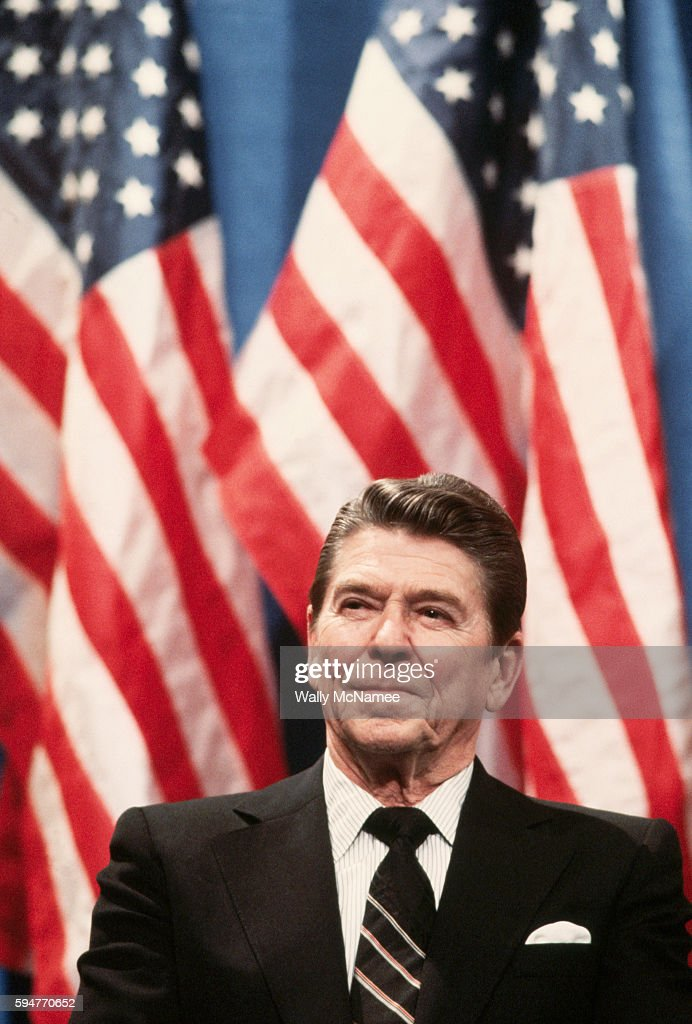 With American flags as a backdrop, President Ronald Reagan waits to speak on behalf of Senate candidate and former astronaut Harrison Schmitt at a rally in Albuquerque.