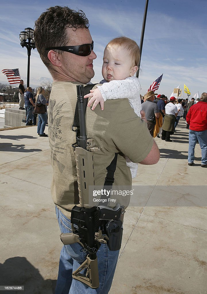 With an AR-15 slung over his shoulder, Bart Davidson holds his six-month-old son Tristan at a gun rights rally and march at the Utah State Capitol on March 2, 2013 in Salt Lake City, Utah. The rally attracted several hundred people for the march to the Utah Capitol in favor of 2nd Amendment rights as gun control supporters call for more limits and bans on assault weapons.