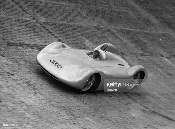 With an AutoUnion racing car Bernd Rosemeyer tests the new North curve of the AVUS in Berlin Apart from him the test drives were also carried out by...