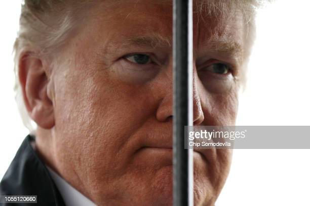 With an umbrella handle in front of his face US President Donald Trump talks to reporters before leaving the White House October 15 2018 in...