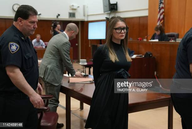 With attorney Todd Spodek and Judge Diane Kiesel in the background fake German heiress Anna Sorokin is led away after being sentenced in Manhattan...