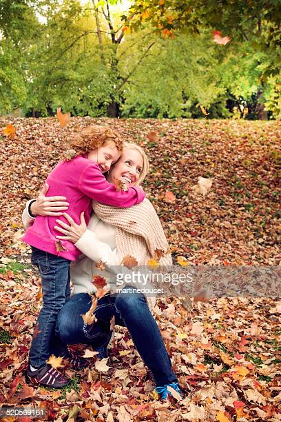 "with autumn's falling leaves, mother and daughter share hug. - ""martine doucet"" or martinedoucet stockfoto's en -beelden"