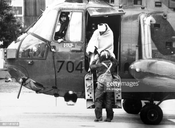 With bandaged head and swathed in a blanket a survivor of the North Sea oil production platform Piper Alpha is helped from a rescue helicopter at...