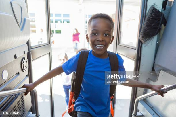 with big a smile, the young boy eagerly boards bus - first day of school stock pictures, royalty-free photos & images