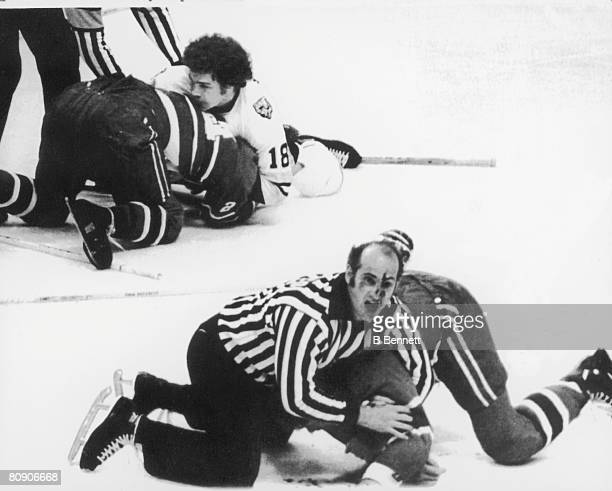 With blood on his face Canadian linesman John D'Amico calls for help as he wrestles Pierre Bouchard of the Montreal Canadiens to the ice after a...