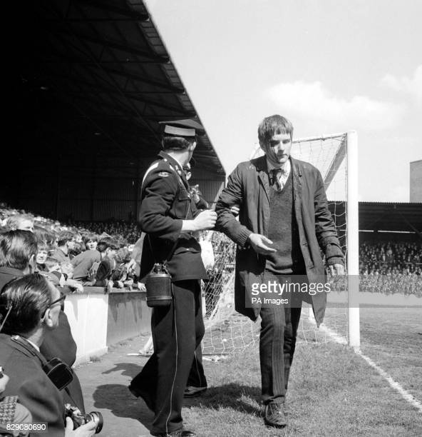 With blood streaming down his face a spectator is guided from the crowd by an ambulance man during the First Division match between West Ham United...