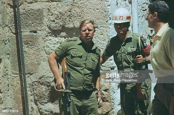 With blood streaming down his face from a cut to his forehead an Israel Defence Force army Lieutenant is helped by a soldier from the gates of the...
