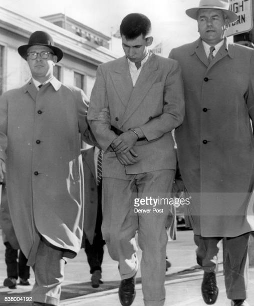 With bowed head and his hands in manacles John Gilbert Graham of 2650 W Mississippi Ave walks between two FBI agents toward the Denver postoffice...