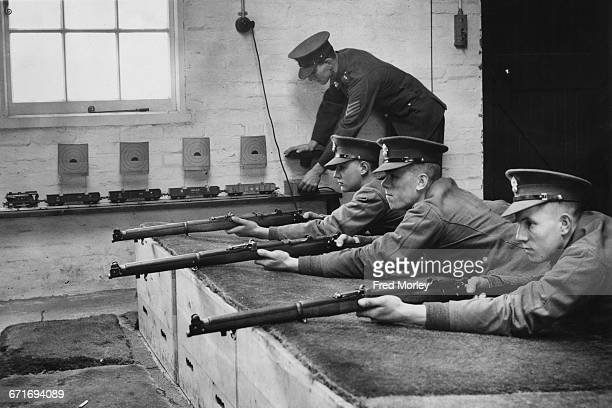 With cardboard shooting targets fixed onto the carriages of an electric model train a sergeant of the Royal Fusilier Regiment prepares to instruct...