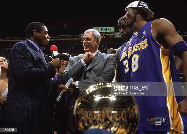 With championship trophy in the foreground head coach Phil Jackson of the Los Angeles Lakers talks with announcer Ahmad Rashad while guard Kobe...