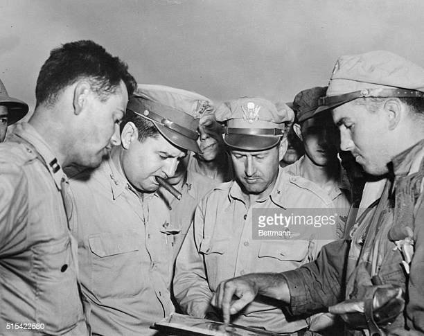 With cigar in mouth Major General Curtis E LeMay the commander of 21st Bomber Command listens as B29 Navigator Lt Nelson McDowell of Philadelphia...
