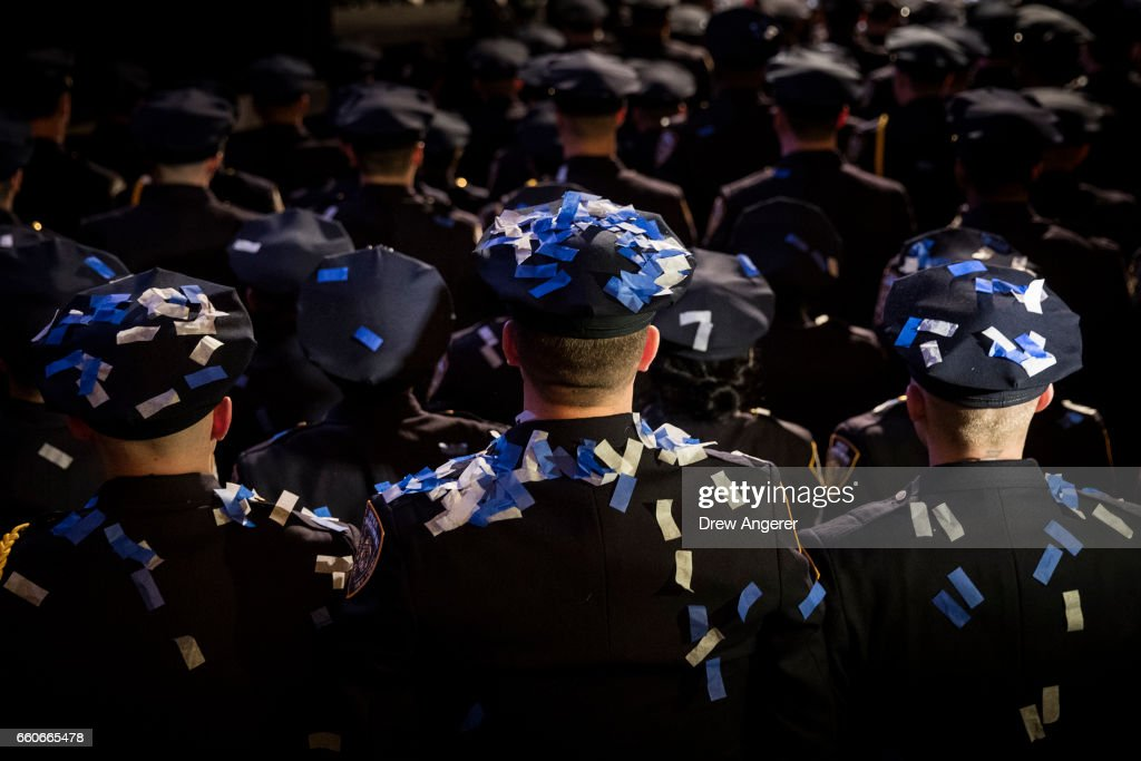 With confetti on their hats and uniforms, the newest members of the New York City Police Department (NYPD) stand at attention at the conclusion of their police academy graduation ceremony at the Theater at Madison Square Garden, March 30, 2017 in New York City. Over 600 new officers were sworn in during the ceremony.