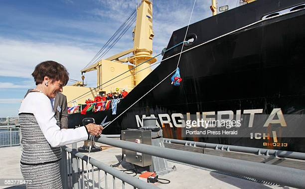 With crew watching on board, Marguerita deLuca of NYC prepares to cut the rope for the christening of the MV Marguerita, for which she became the...