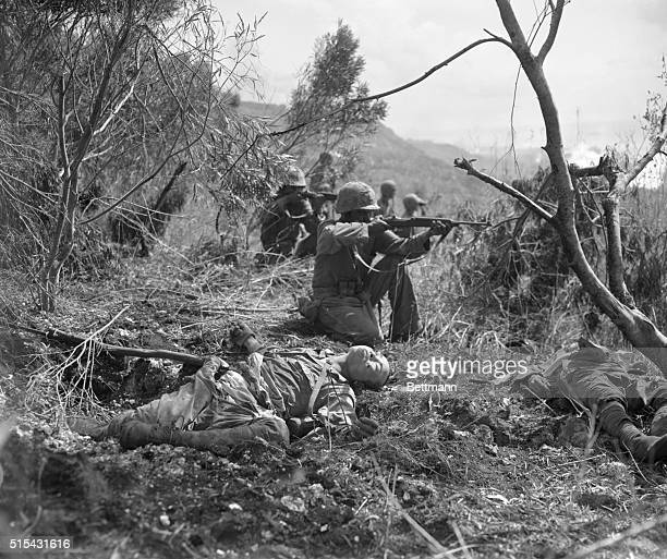 With dead Japanese soldiers nearby, Marines aim at the enemy downhill during the U.S. Invasion of Saipan.