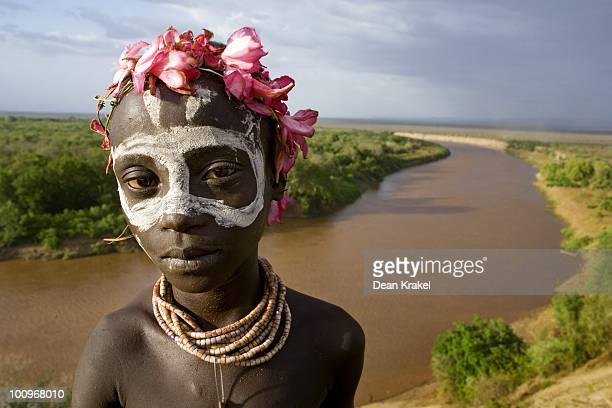 With decorative blossoms from the Elephant Tree in his hair a young Karo boy stands above the Omo River near the village of Kolcho in the Lower Omo...