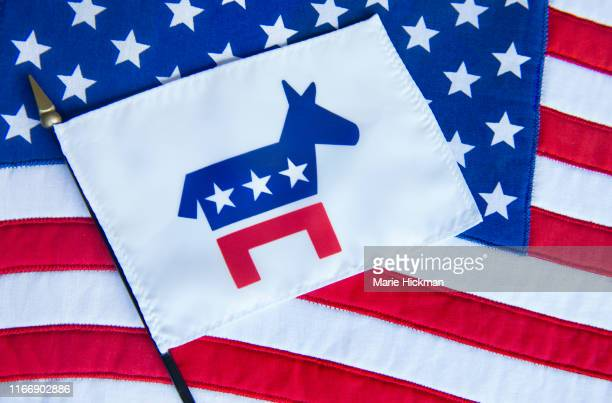 democratic party flag with donkey as its' symbol laying on an american flag. - democratic party usa stock pictures, royalty-free photos & images