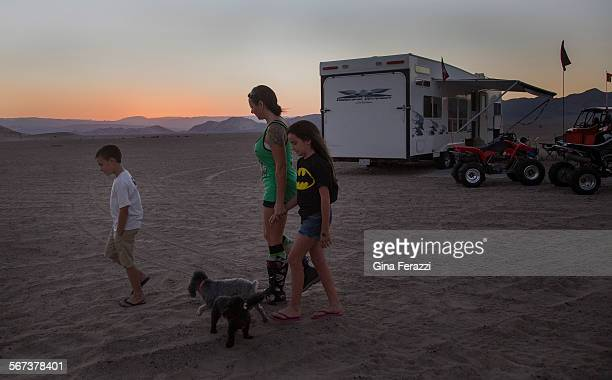With dusk settling in Amy Miles of Apple Valley walks with her children Kailah and Rex near the family's campsite at the Dumont Dunes on October 9...