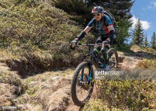 with electric mountainbike on bumpy single trail in the carinthian mountains, austria. - bumpy stock photos and pictures